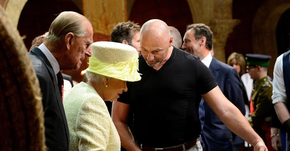 24.jun.2014 - A Rainha Elizabeth 2ª e o marido, o Príncipe Philip, olham acessórios e figurinos de
