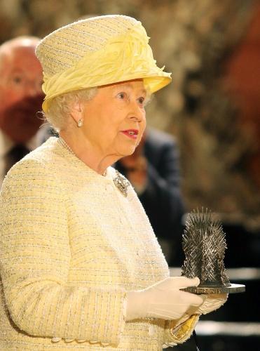24.jun.2014 - A Rainha Elizabeth 2ª ganha miniatura do Trono de Ferro durante visita ao set de