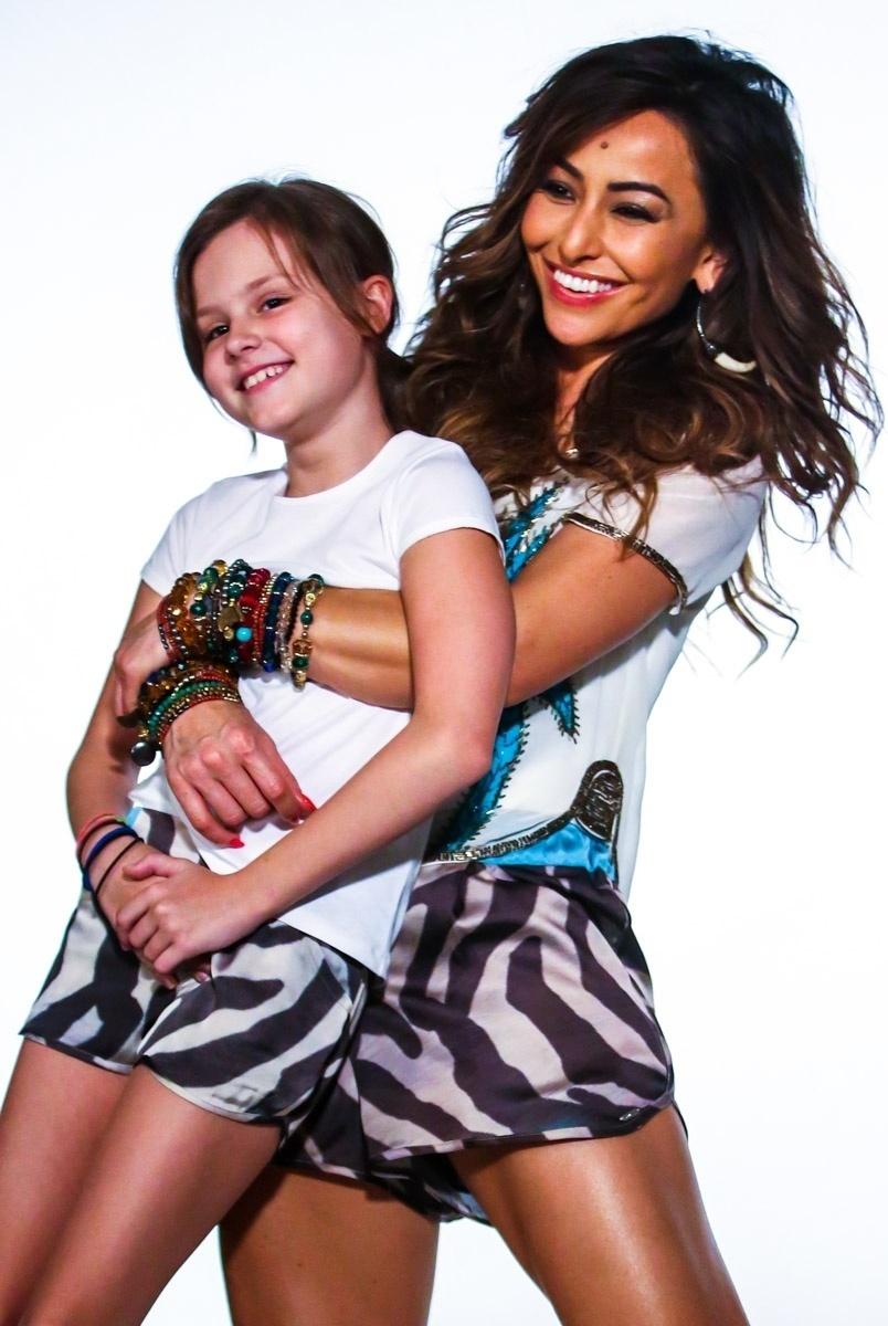 24.jun.2014 - Com um shortinho e uma blusa, Sabrina Sato segura modelo no colo durante ensaio para uma campanha publicitária de uma marca de roupas feminina, em São Paulo