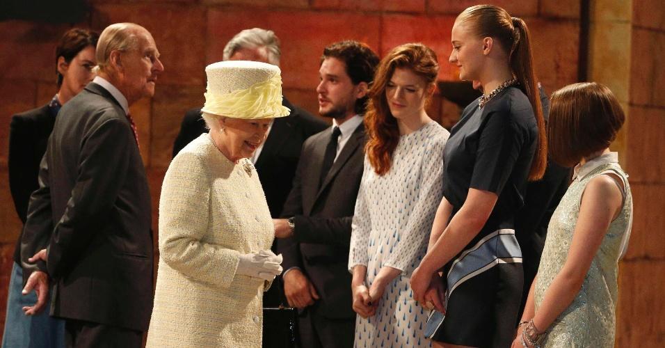 24.jun.2014 - Rainha Elizabeth 2ª cumprimenta os atores Kit Harrington, Rose Leslie e Sophie Turner durante sua visita ao set de filmagens da série