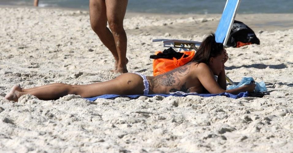25.jun.2014 - A ex-modelo Cristina Mortágua faz topless e deixa tatuagens à mostra enquanto toma sol na praia da Barra da Tijuca, no Rio de Janeiro