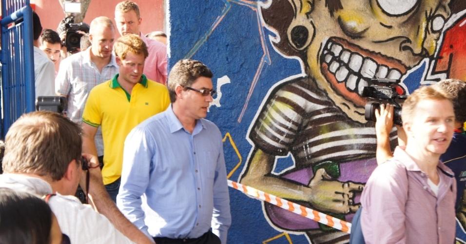 25.jun.2014 - Com a camisa do Brasil, Príncipe Harry chega a quadra de futebol em Diadema