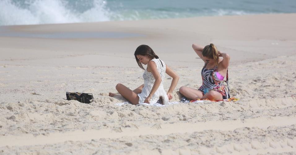 26.jun.2014 - Acompanhada por amiga, Isis Valverde coloca vestido na praia da Reserva, no Rio de Janeiro