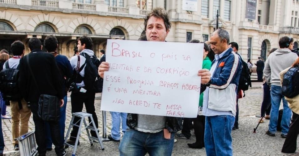 26.jun.2014 - Com cartaz, homem faz protesto durante a visita do Príncipe Harry à Cracolândia, em São Paulo. No papel, estava escrito: