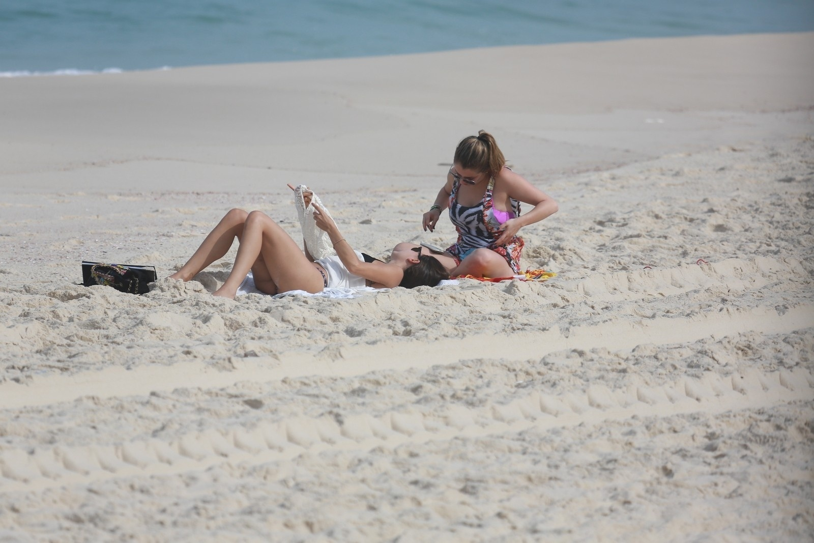 26.jun.2014 - Isis Valverde conversa com amiga enquanto toma sol na praia da Reserva, no Rio de Janeiro