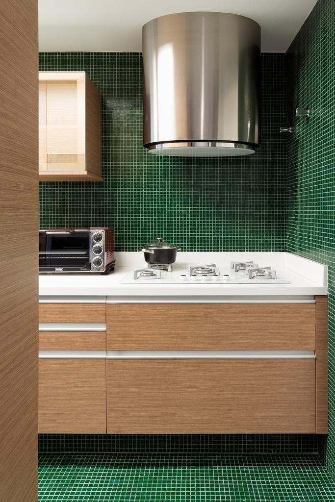 Contemporânea, a cozinha planejada por Diego Revollo foi totalmente revestida com pastilhas verdes, compondo com a madeira e o aço escovado. Apesar de escura, a cor do revestimento é viva