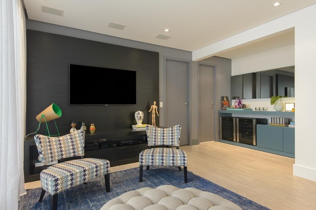 O living integrado ao home theater, planejado pelo escritório D2N Arquitetura e Interiores, mescla cores sóbrias às contemporâneas, como as nuanças de cinza ao azul mais claro. O branco como base em parte das paredes e no forro e a madeira clara no piso balanceiam a composição, se contrapondo à marcenaria escura e dão forma a um espaço jovem e descontraído