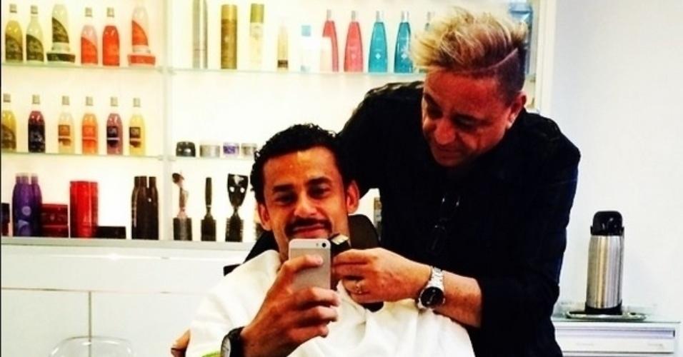 27.jun.2014 - O atacante da Seleção Fred apara o bigode com um barbeiro.