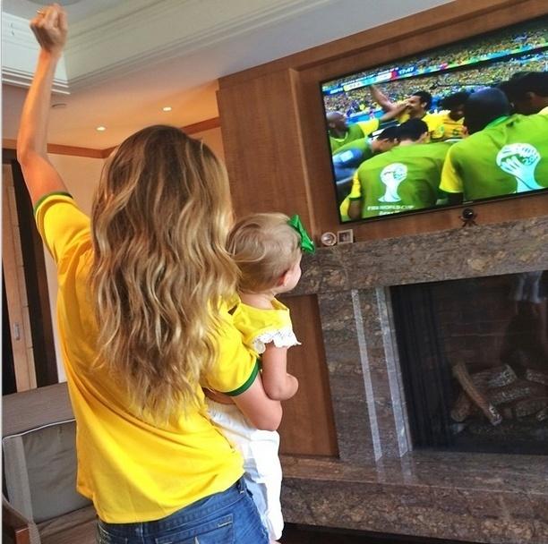 28.jun.2014 - Com a filha Vivian no colo, Gisele Bündchen comemora o primeiro gol do Brasil contra o Chile
