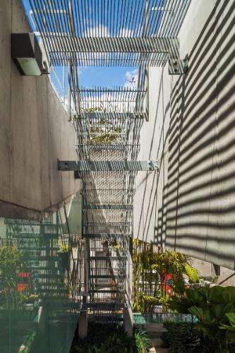 A escada metálica situada entre o bloco dos dormitórios e a piscina foi executada em perfis vazados de aço galvanizado a fogo, o que permite franca passagem de luz natural para os jardins no nível inferior. A Casa de Fim de Semana foi projetada pelo escritório SPBR Arquitetos