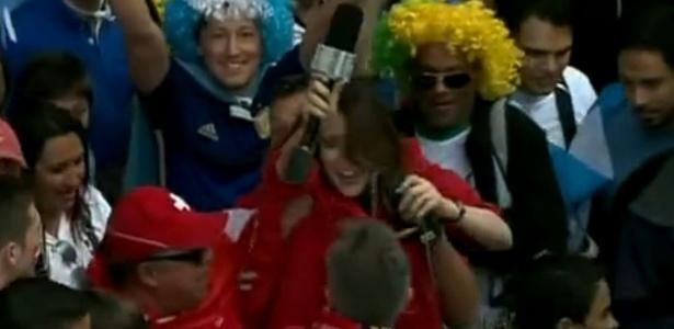 """Durante entrada """"ao vivo"""" no """"Encontro"""", da Globo, repórter é """"levantada"""" por torcedores suíços"""