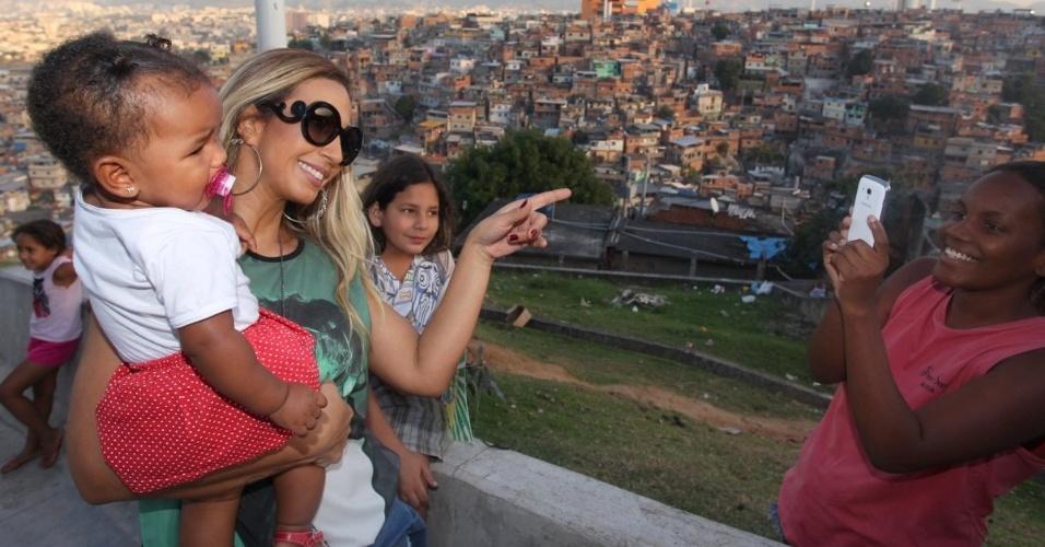 3.jul.2014- Valesca Popozuda é tietada durante visita no Complexo do Alemão