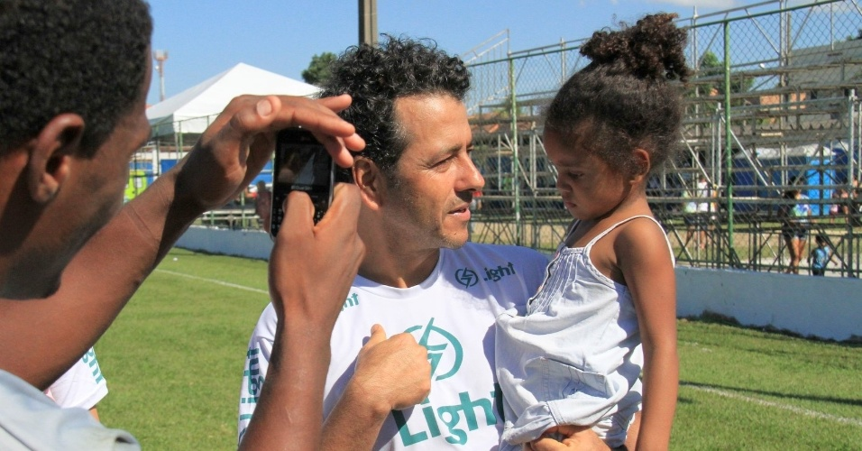6.jul.2014 - O ator Marcos Palmeira tira foto com criança durante partida de futebol beneficente em Itaguaí, no Rio