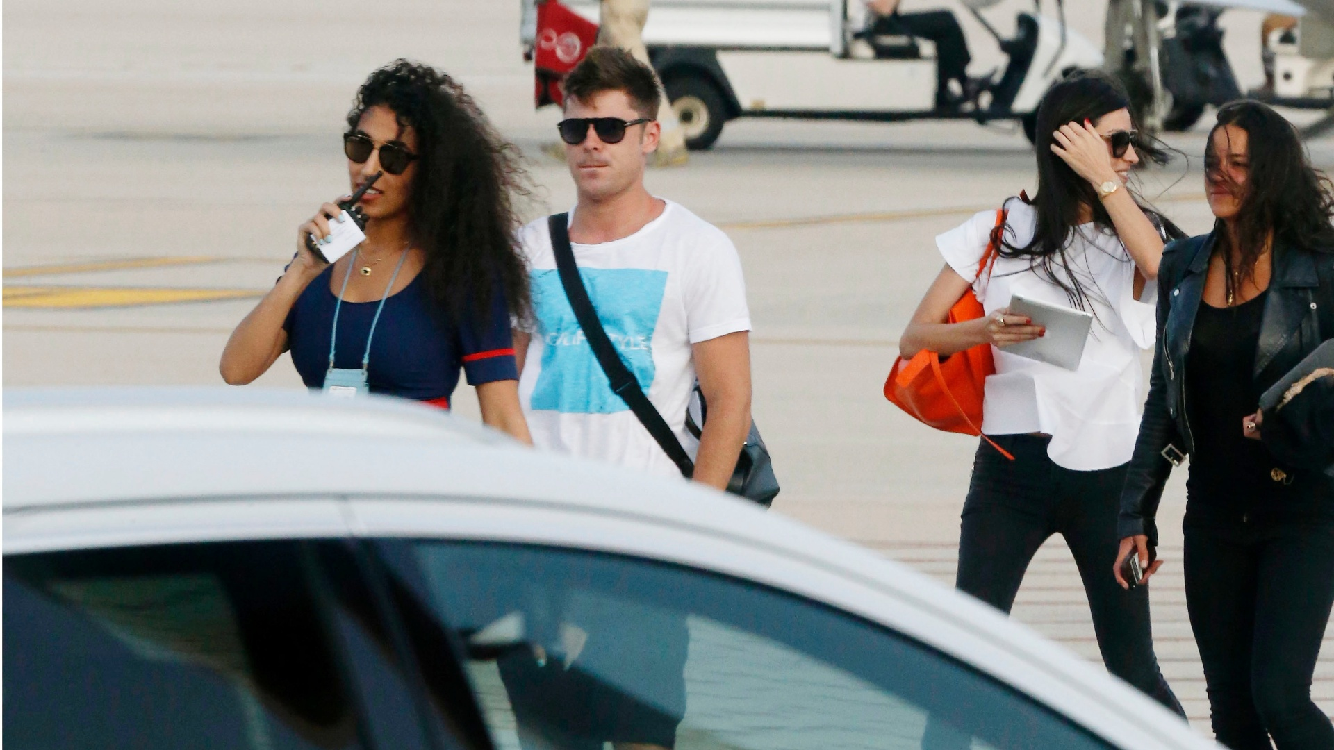 3.jul.2014 - Zac Efron e Michelle Rodriguez (à direita, de preto) desembarcam na Sardenha, na Itália