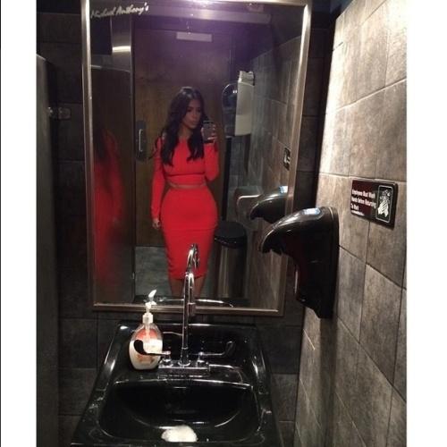 7.jul.2014 - Kim Kardashian se rendeu a foto selfie dentro de um banheiro. A socialite e empresária divulgou o registro na internet e contou que o look vermelho faz parte de sua nova coleção de roupas