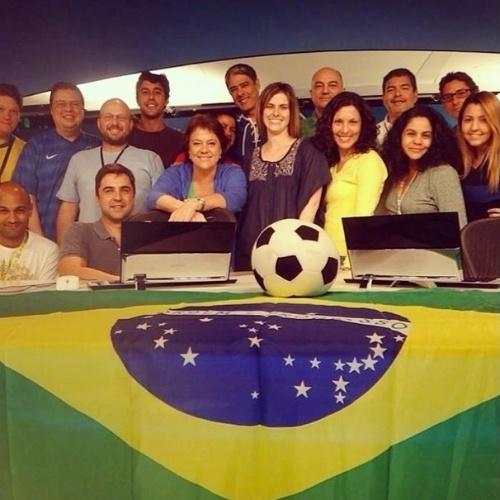 """8.jul.2014 - William Bonner se reuniu com a equipe do """"Jornal Nacional"""" para acompanhar o jogo entre Brasil e Alemanha. A bancada da telejornal foi coberta por uma bandeira do Brasil"""
