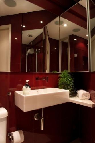 A solução para aumentar a sensação de espaço no banheiro, muito pequeno, foi instalar diversos espelhos, que revestem trechos da parede e a porta do armário, em frente ao boxe (onde está refletida a imagem do chuveiro elétrico). O