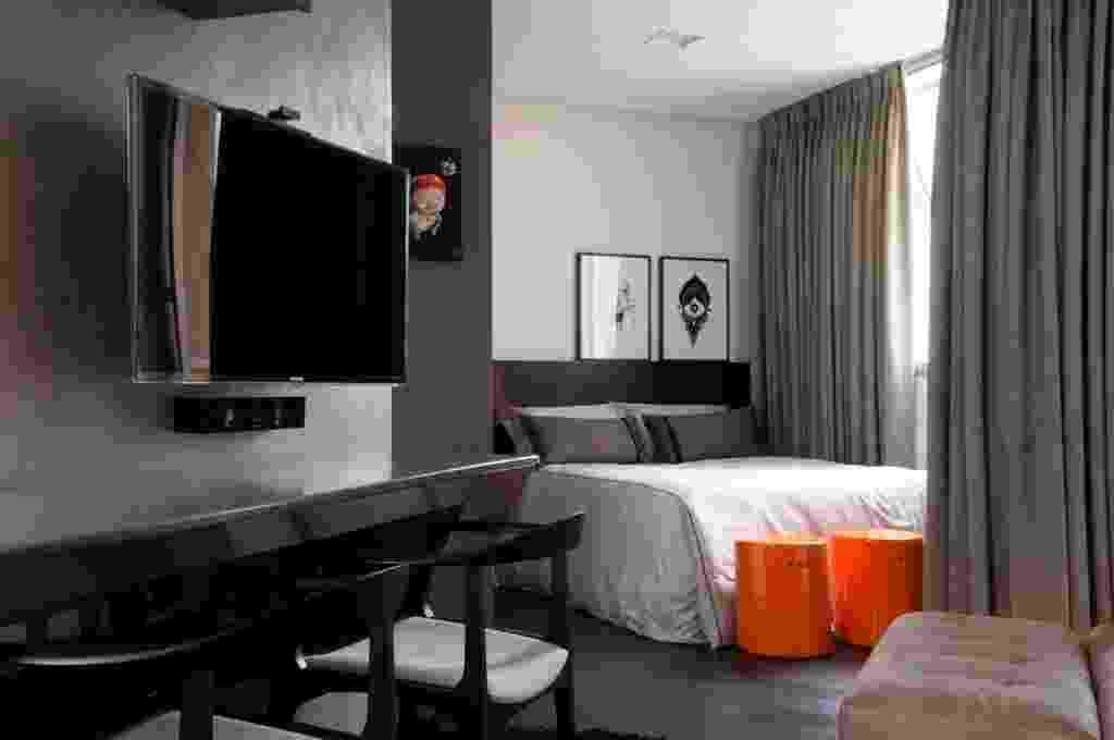 """O dormitório está integrado à sala de estar e dela se separa apenas por uma cortina em veludo cinza (Luci-Cortinas), cujo trilho corre desde o canto da janela (à dir.) e em """"L"""". No estar, a bancada em MDF laqueado (Contexto Oficina da Madeira) na cor cinza mantém a paleta cinzenta que também se apresenta no piso em PVC, dando unidade ao quarto e à área social, a fim de ampliar o espaço exíguo, de 27 m². A reforma do apartamento Jardins, em São Paulo, foi projetada por Ricardo Abreu Borges - Marcelo Magnani/ Divulgação"""