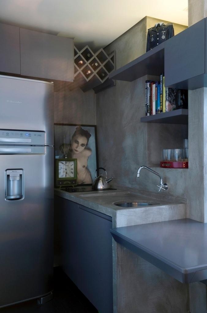 A pia original em granito, do apartamento Jardins, recebeu pintura espatular que imita o cimento queimado (Mr. Cryl). A marcenaria, em MDF laqueado cinza, é integrada à da sala de estar, através de módulos suspensos, e cria armários e nichos na parede que divide o banheiro e a cozinha. O espaço foi pensado para encaixar a geladeira Electrolux grande (à esq.) e um cooktop de vidro Tramontina, com duas bocas. A reforma tem projeto assinado pelo arquiteto Ricardo Abreu Borges
