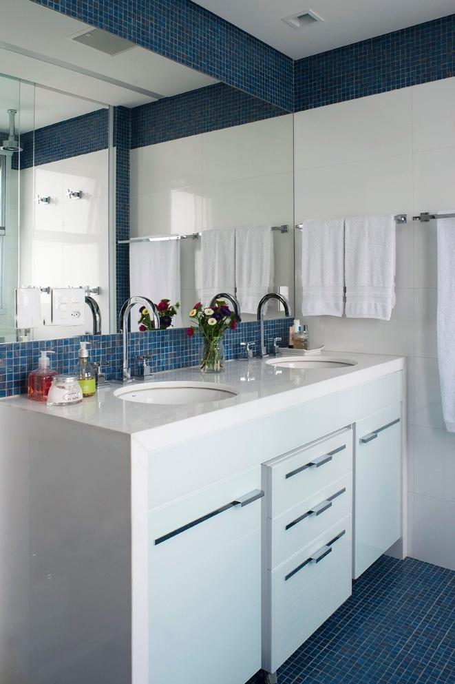 A bancada em mármore piguês e o gabinete são brancos e contrastam com o azul das pastilhas de vidro. As duas cubas trazem conforto e harmonia para o uso conjunto do casal. O apê FMS tem projeto de reforma do escritório KTA Arquitetura