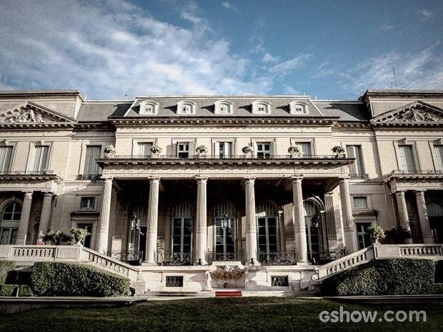 A fachada da mansão é monumental, com pilastras imponentes e pé direito altíssimo
