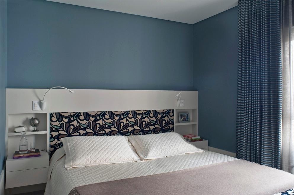 O dormitório do casal exibe uma atmosfera suave, com paredes pintadas de azul índigo que se alinham com a estampa do tecido da cabeceira (Donatelli) e das cortinas. A marcenaria em laca