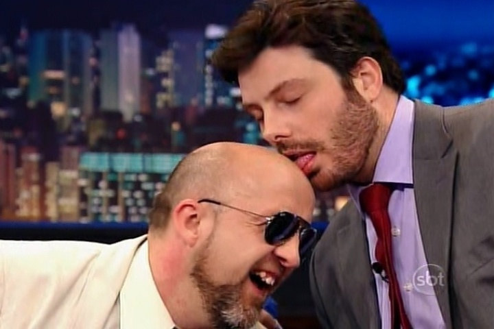 15.jul.2014 - Danilo Gentili dá uma lambida na cabeça do apresentador Fabrício Carpinejar durante entrevista no