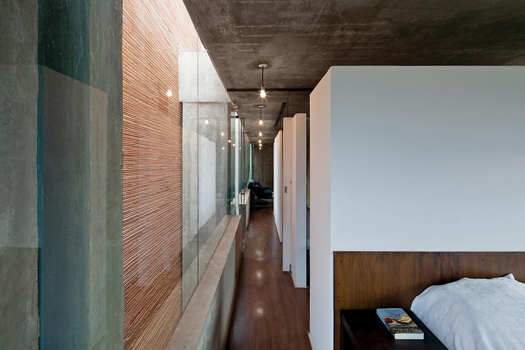 Assim como o vão sul (à esq.), o corredor que liga todos os ambientes internos da House in the Air tem 16 m de comprimento. Entre os volume principal flutuante que abriga os cômodos e as duas caixas suspensas que funcionam como contrapeso, estão dois pilares de seção 0,27 m x 0,8 m, em concreto armado, que suportam toda a residência