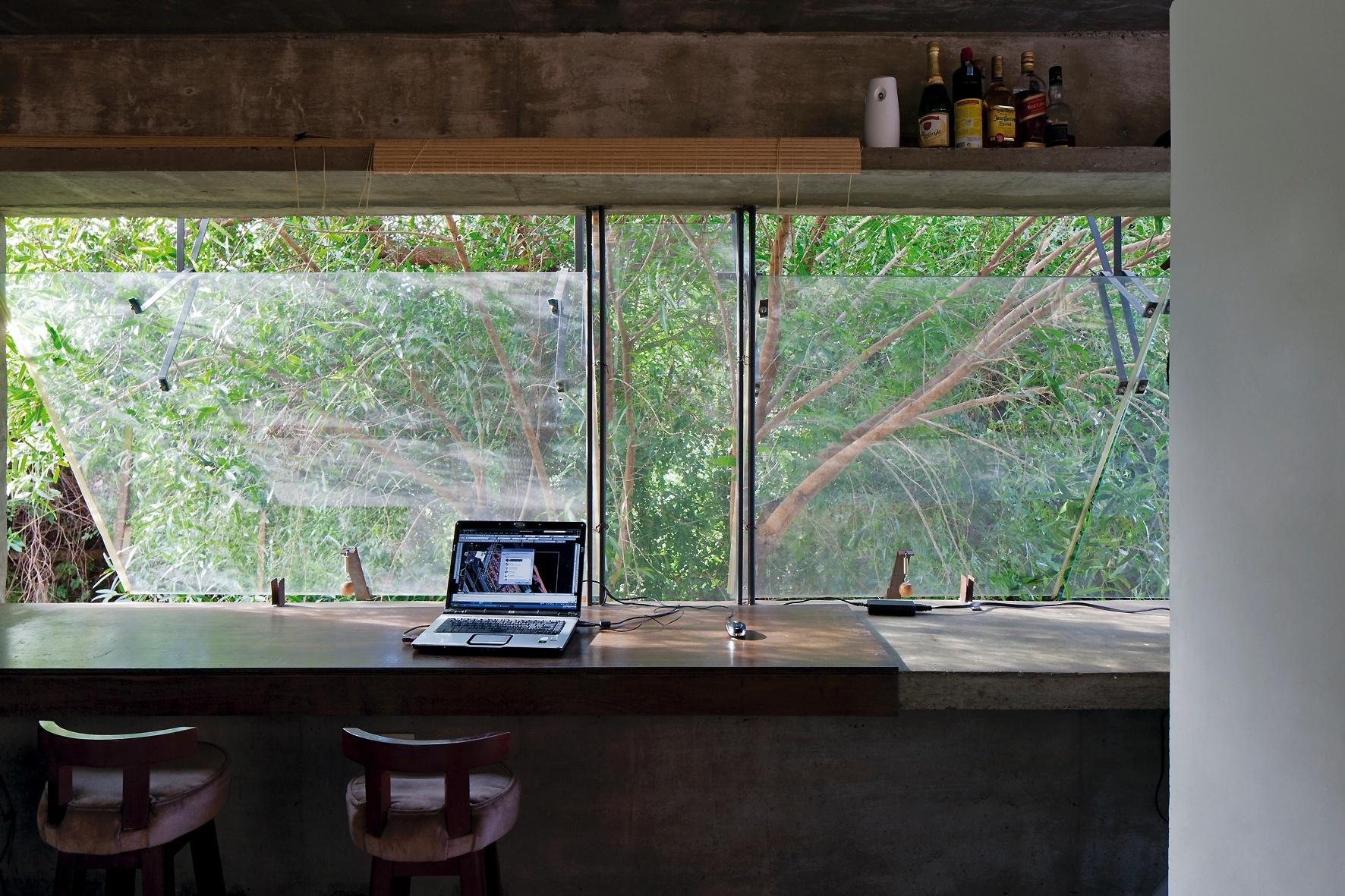 Na face norte, o volume principal da House in the Air se abre para a vegetação. As vigas de apoio acompanham todo o vão, como prateleira (acima) ou grande bancada (abaixo), ambas com 16 m de comprimento. A inferior serve para café da manhã, apoio de cozinha ou mesa de trabalho e estudos, pois é um elemento comum a todos os ambientes. O sistema máximo-ar para janelas é inspirado no modelo empregado por Paulo Mendes da Rocha. A casa tem projeto de arquitetura da TDA e fica no Paraguai