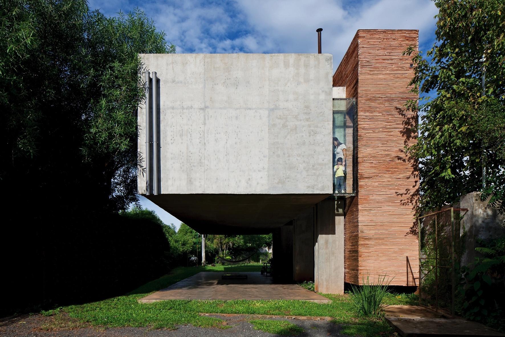 Limpeza estrutural é a característica principal desta casa paraguaia, que tem salas de jantar e estar, dormitórios, cozinha e banheiro concentrados em um bloco totalmente suspenso (à esq.), a partir de dois pilares conectados a um bloco de serviços e outro de circulação (de cerâmica), que servem como contrapeso ao volume. O protagonista é o concreto armado e o balanço da estrutura permite a criação de uma área de convivência, sob a residência. A House in the Ai tem projeto da TDA Arquitetura