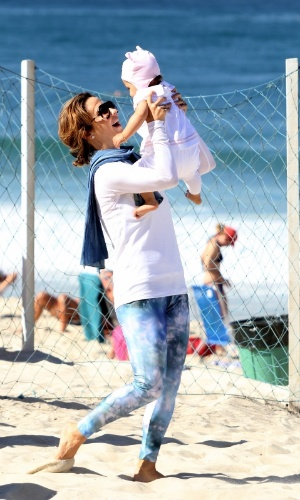 23.jul.2014 - A atriz Guilhermina Guinle pega a filha Minna no colo durante passeio na praia de Ipanema, na zona sul do Rio