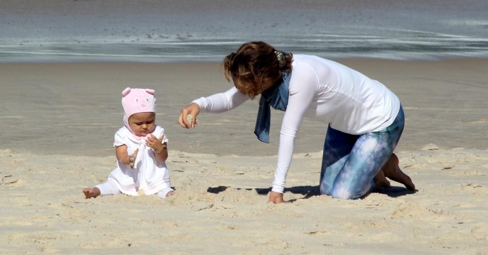 23.jul.2014 - Guilhermina Guinle brinca com a filha Minna na areia praia de Ipanema, na zona sul do Rio