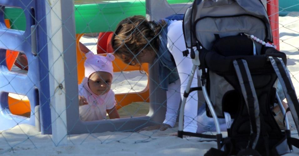 23.jul.2014 - Guilhermina Guinle brinca com a filha Minna no parquinho infantil da praia de Ipanema, na zona sul do Rio