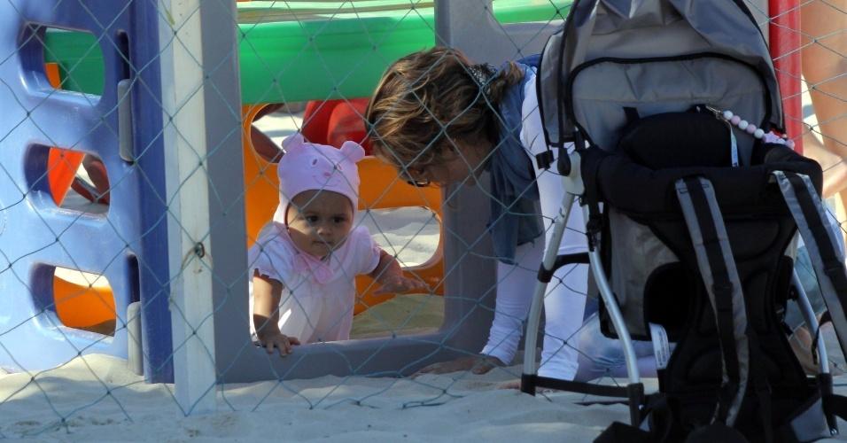 23.jul.2014 - Guilhermina Guinle brinca com a filha Minna, que usa um gorro de bichinho, no parquinho infantil da praia de Ipanema, na zona sul do Rio