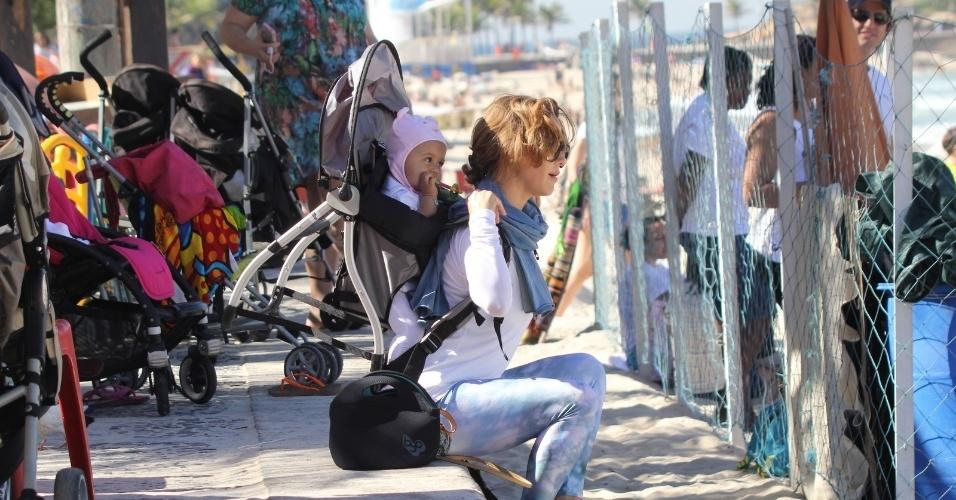 23.jul.2014 - Guilhermina Guinle caminha com a filha Minna, presa no carrinho de bebê, na praia de Ipanema, na zona sul do Rio