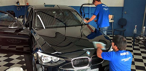Funcionários da Acquazero fazem lavagem a seco de um BMW: serviço promete gastar no máximo um litro de água, mas sofre com a fama de que pode riscar o carro