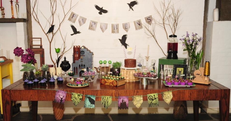 A mesa ficou completa com a disposição de castiçais, velas, vasos, plantas e flores, organizada pela Flamingo em Festa. Dois vasos com galhos secos enfatizam o clima de mistério, emoldurando as bandeiras com letras que formam a palavra