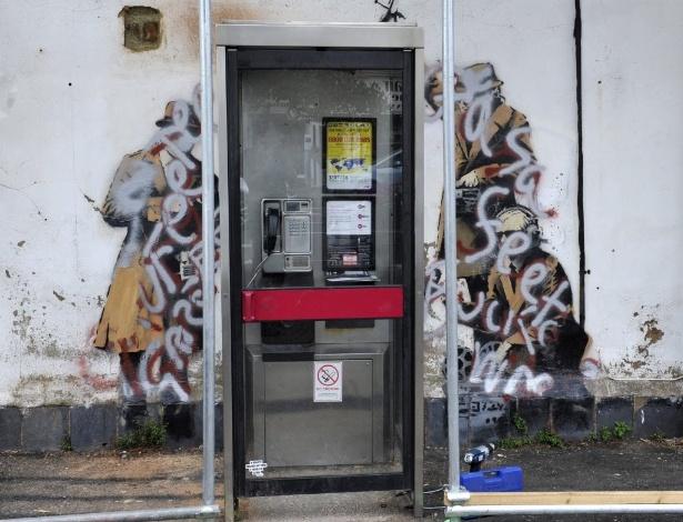 """01.ago.2014 - Obra de Bansky que mostra homens """"espionando"""" cabine telefônica é pichada em Cheltenham, na Inglaterra - EFE"""