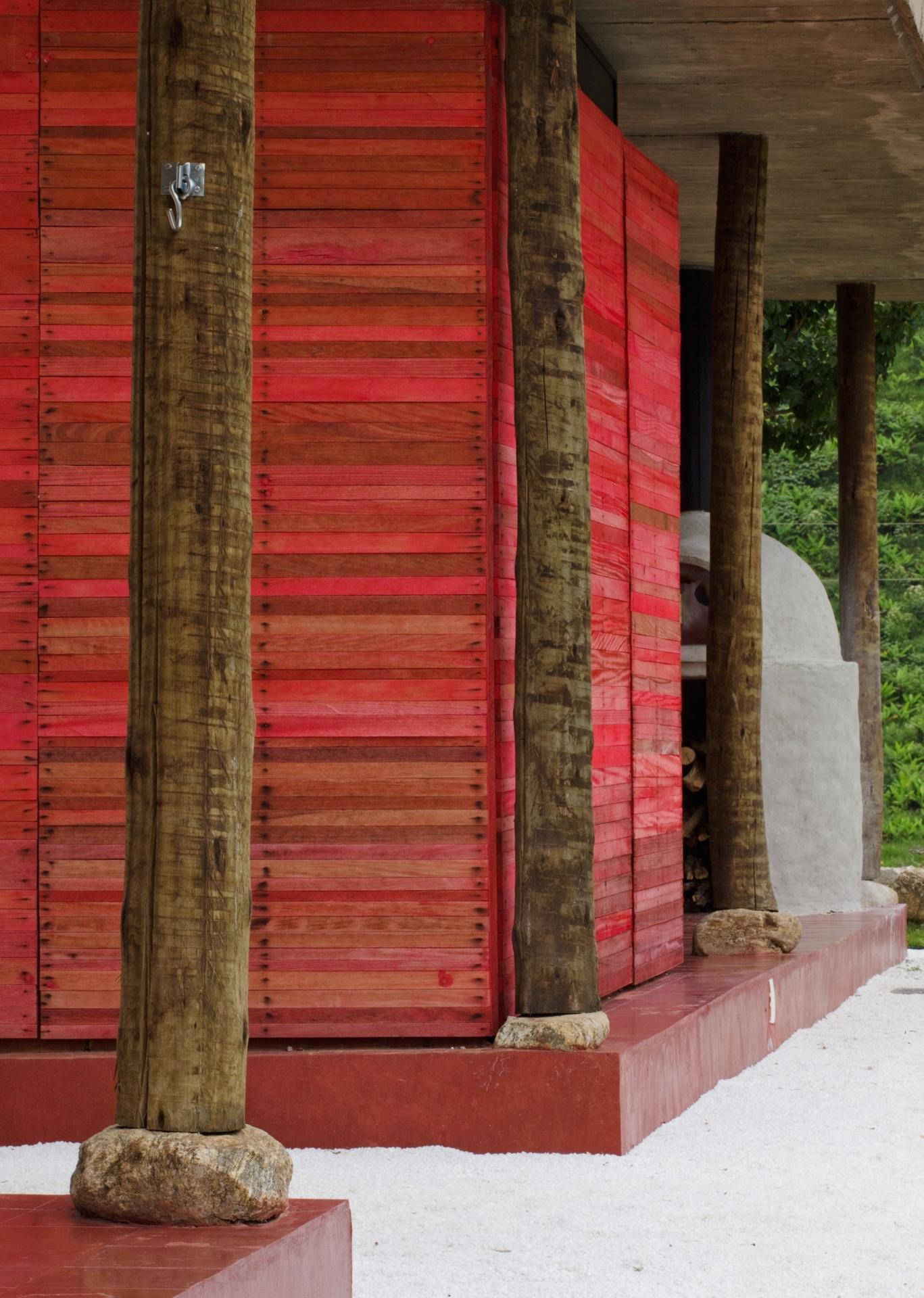O pequeno lavabo foi implantado na varanda da casa Dom Viçoso, projetada pelo arquiteto Marcelo Ferraz. Em alvenaria, o volume foi revestido com madeira e pintado em vermelho, contrastando com as paredes caiadas da casa. Destaque para as colunas de eucalipto