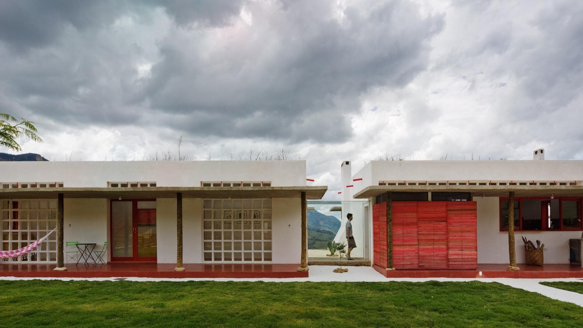 Os dois volumes da casa Dom Viçoso, projetada pelo arquiteto Marcelo Ferraz, são interligados por um passadiço envidraçado, indispensável nos dias de chuva. Contrastando com o branco das paredes caiadas, o arquiteto projetou um lavabo na varanda, pequeno volume em alvenaria revestido de madeira e pintado em vermelho