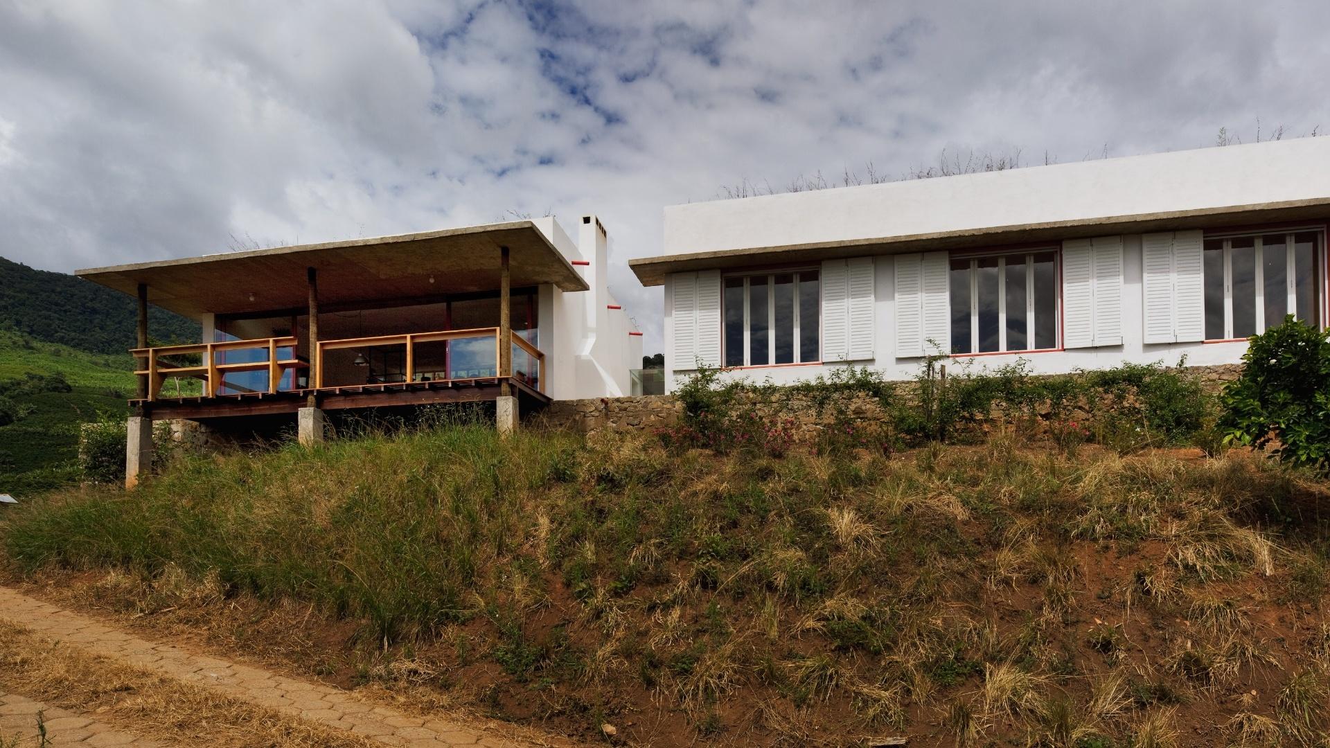 Os dois blocos da casa Dom Viçoso, projetada pelo arquiteto Marcelo Ferraz, têm formatos distintos: à direita, é possível ver os amplos janelões das três suites com beiral; à esquerda, está o volume da área social com varanda voltada para as montanhas