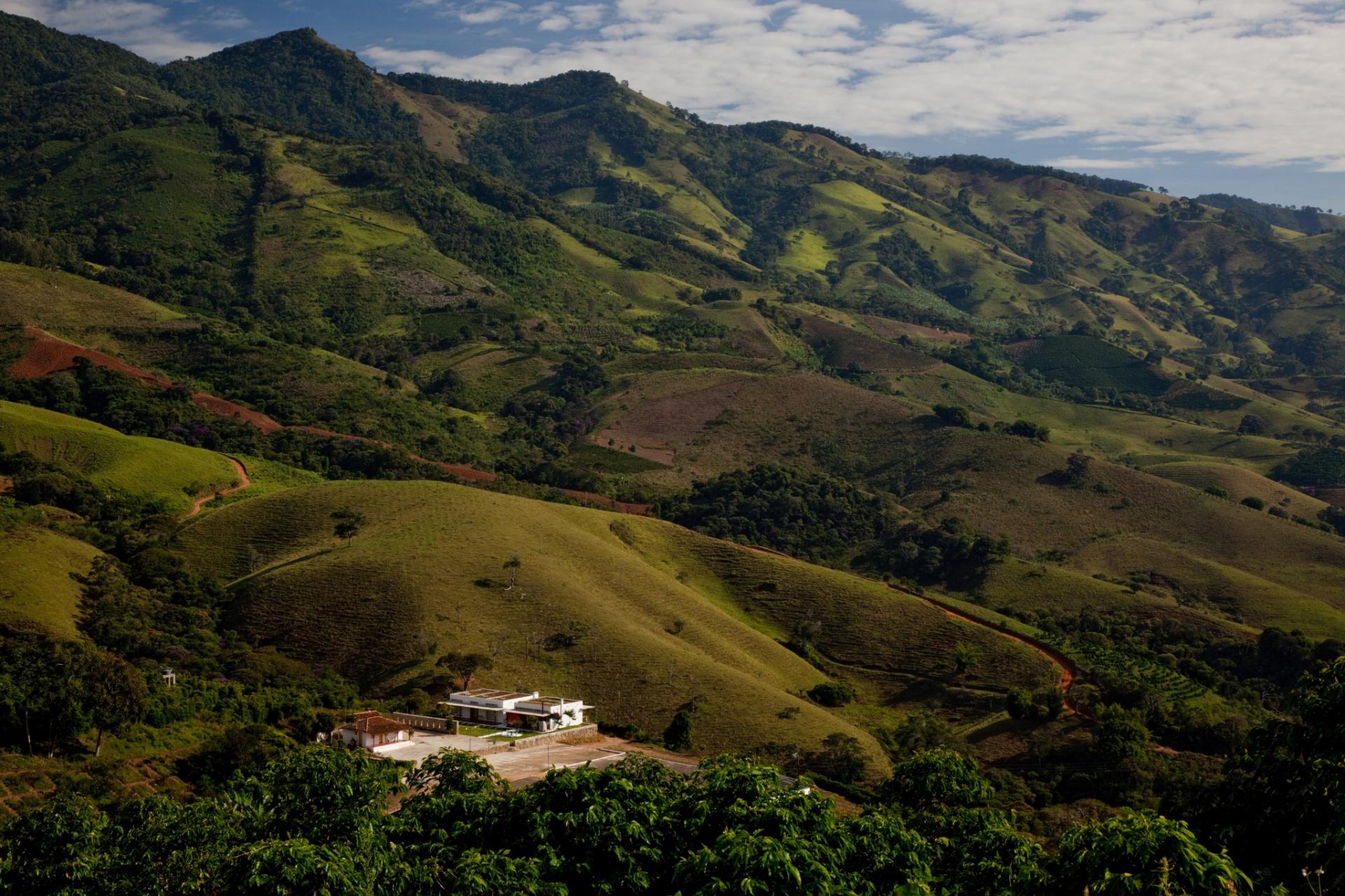 A paisagem montanhosa domina o cenário onde está casa Dom Viçoso, projetada pelo arquiteto Marcelo Ferraz. A construção aparece como um pequeno ponto branco em meio ao verde das serras