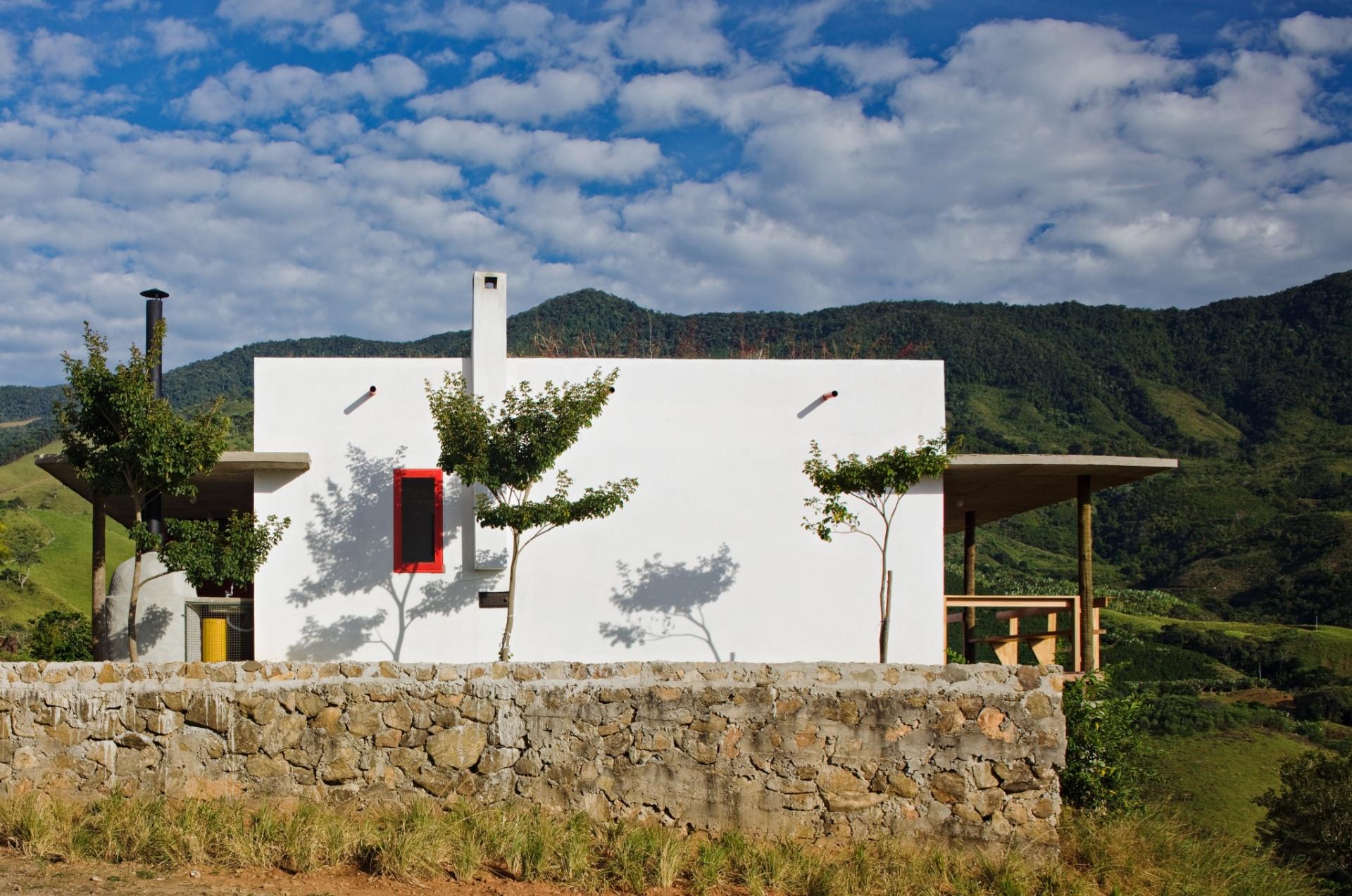 Como um quadro sobreposto à paisagem, a casa Dom Viçoso, projetada pelo arquiteto Marcelo Ferraz, exibe a empena cega da sala de estar, a varanda que olha para o vale e o forno a lenha. Em primeiro plano, o muro de pedras que delimita o lote