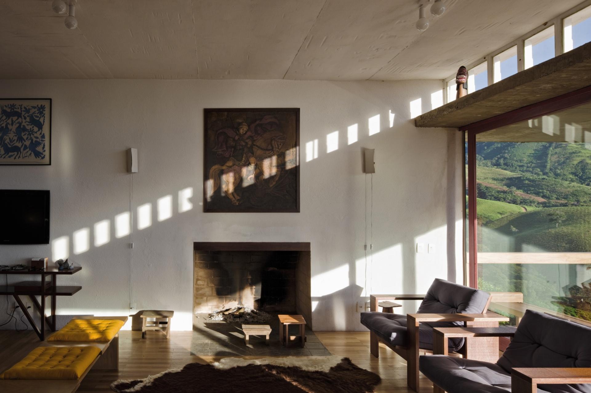 Ao pé da lareira, o recanto de estar apresenta um clima intimista e aconchegante. Na parede, a pintura caiada se alinha aos móveis rústicos e ao piso de madeira, que completa a cena da casa Dom Viçoso projetada pelo arquiteto Marcelo Ferraz