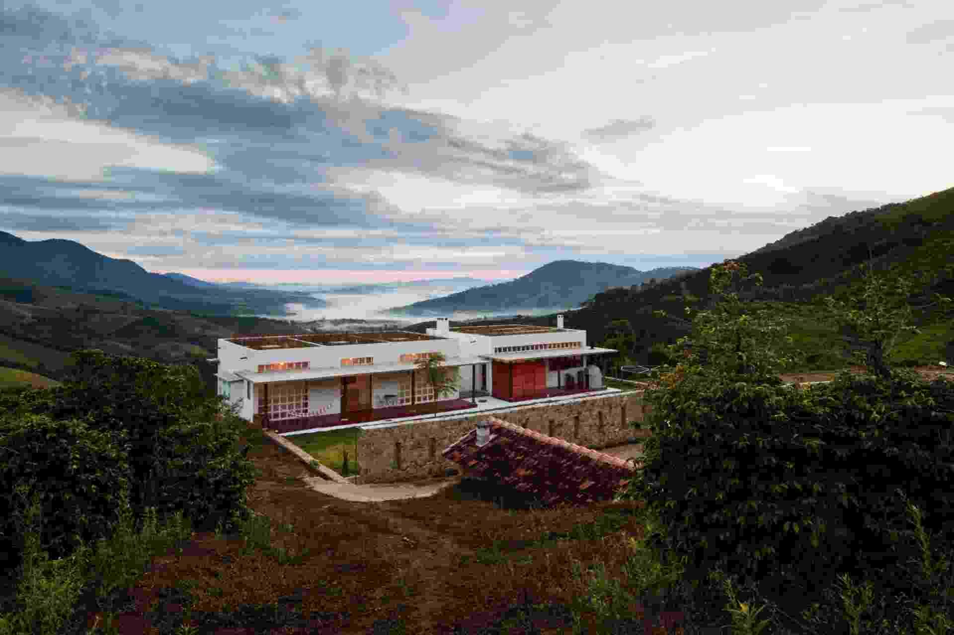 Na casa Dom Viçoso, com projeto do arquiteto Marcelo Ferraz, o espaço da cobertura - com laje plana de concreto e vigamento invertido - recebeu terra e vegetação. O muro de concreto ciclópico com aberturas delimita os espaços da casa-sede e da de hóspedes - Nelson Kon/ UOL