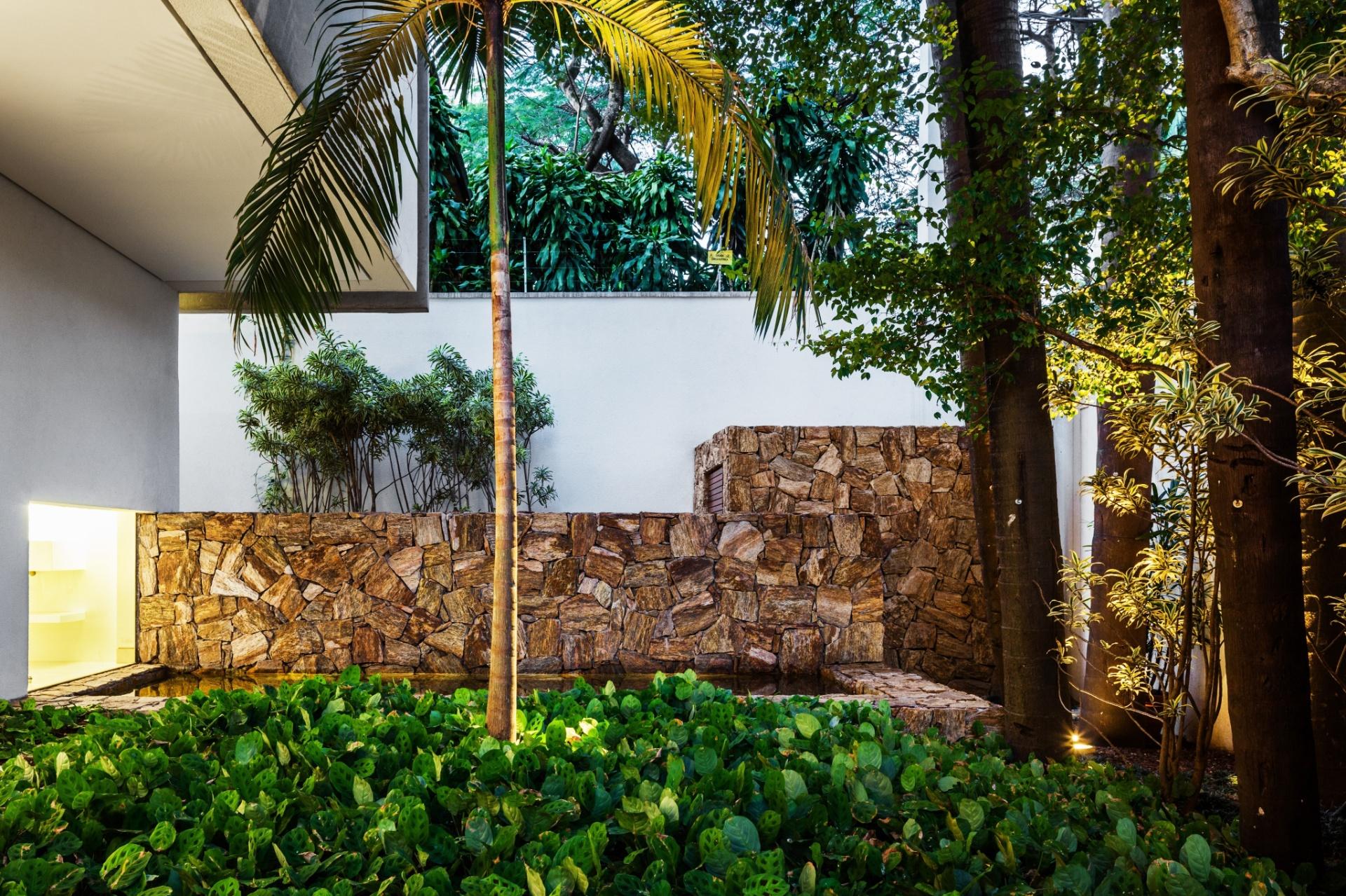 A forração verde, idealizada pela paisagista Martha Gavião, emoldura as árvores de grande porte. Aqui a iluminação foi fundamental para destacar as texturas. A mureta de pedras delimita o acesso de serviço da casa projetada pelo escritório Reinach Mendonça Arquitetos Associados