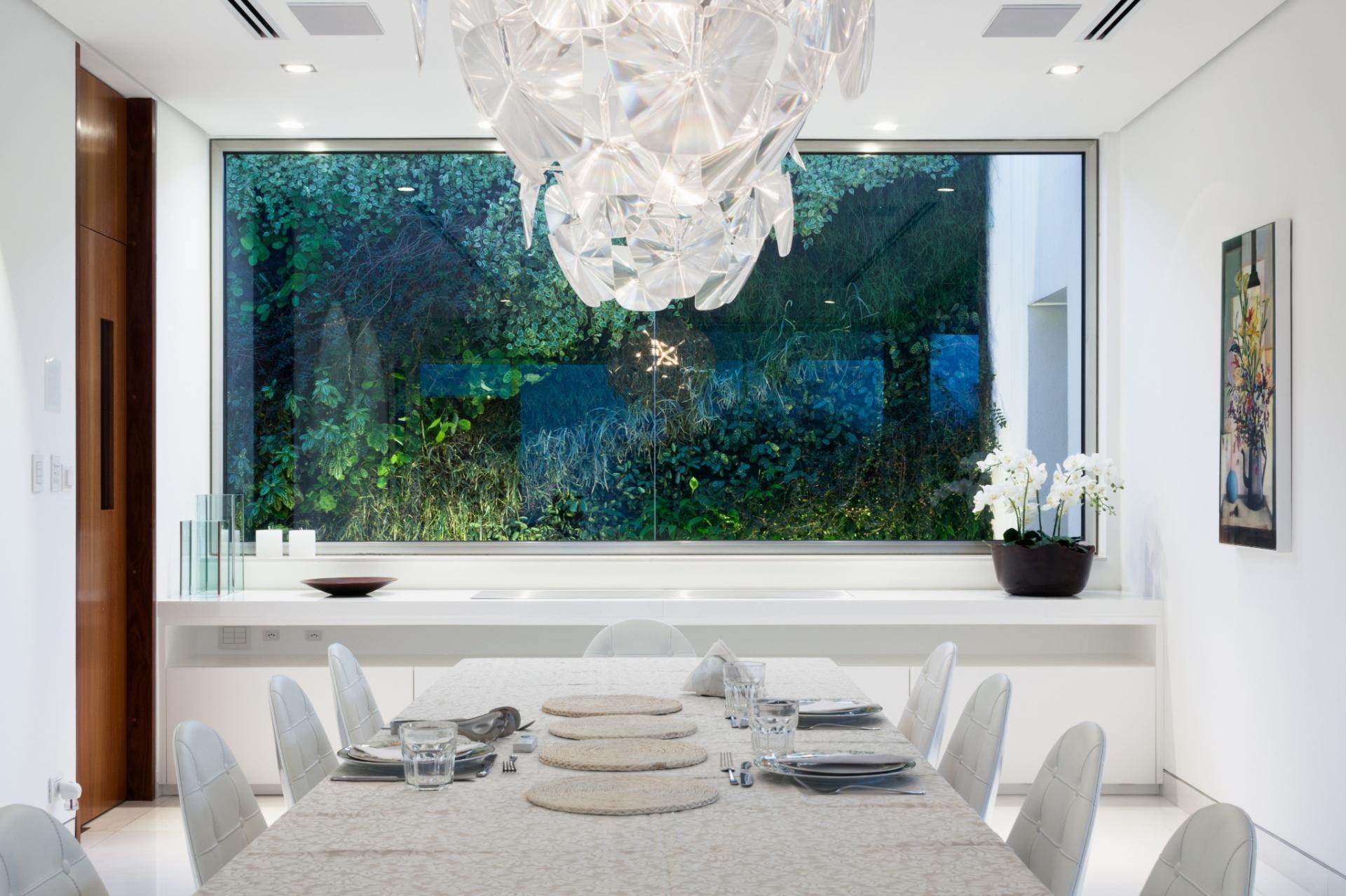 Na sala de jantar contemporânea uma abertura com vidro fixo oferece um quadro natural e verde para decorar o interior. O lustre da Lumini, além de iluminar, destaca-se como elemento decorativo. À esquerda, a porta vai-e-vem acessa a copa da casa projetada pelo escritório Reinach Mendonça Arquitetos Associados