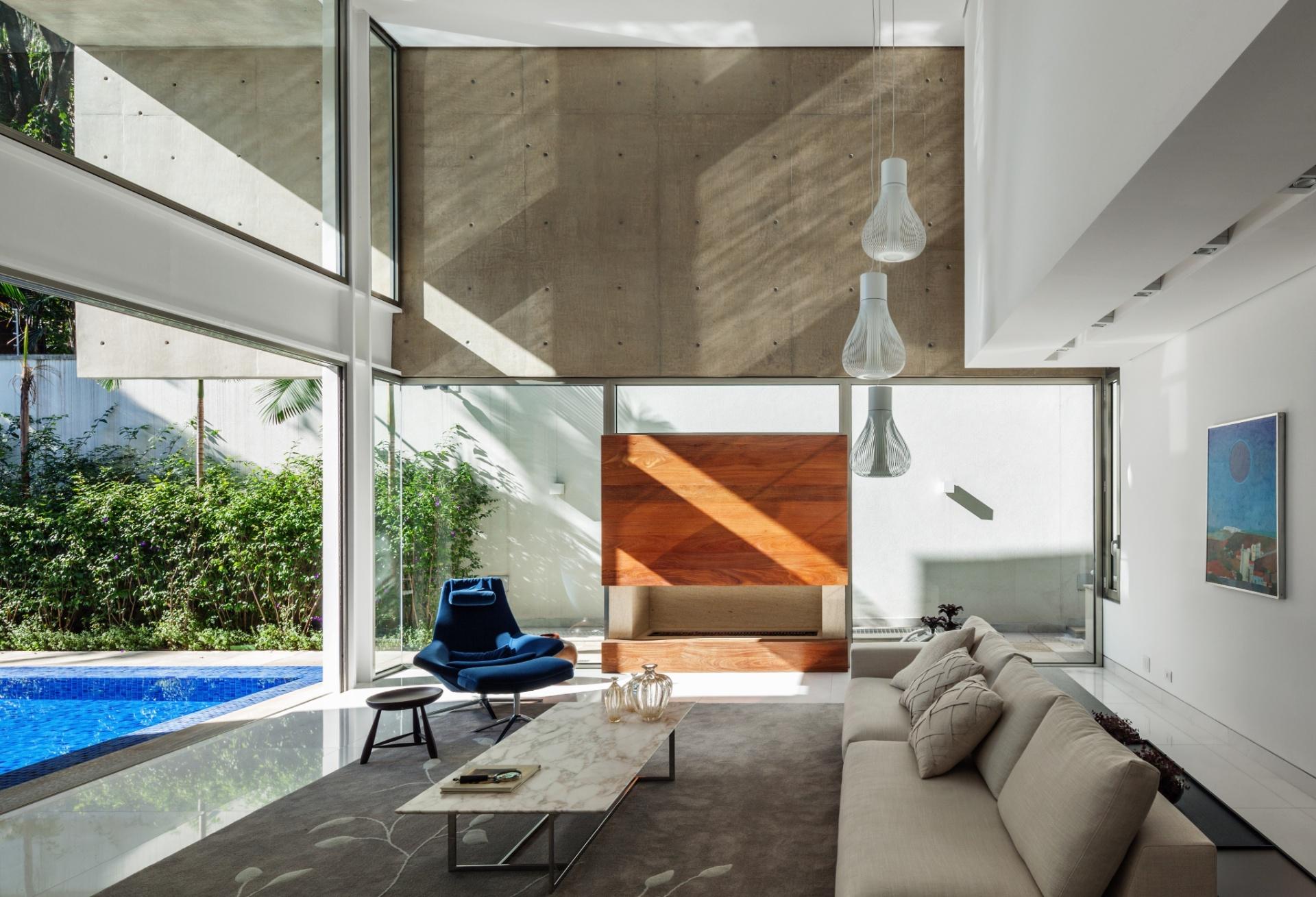A sala de estar com pé-direito duplo é arejada e recebe com elegância os pendentes da Lumini e o mobiliário em linhas modernas. A lareira com frontão de madeira não só aquece o ambiente nos dias de baixas temperaturas, como