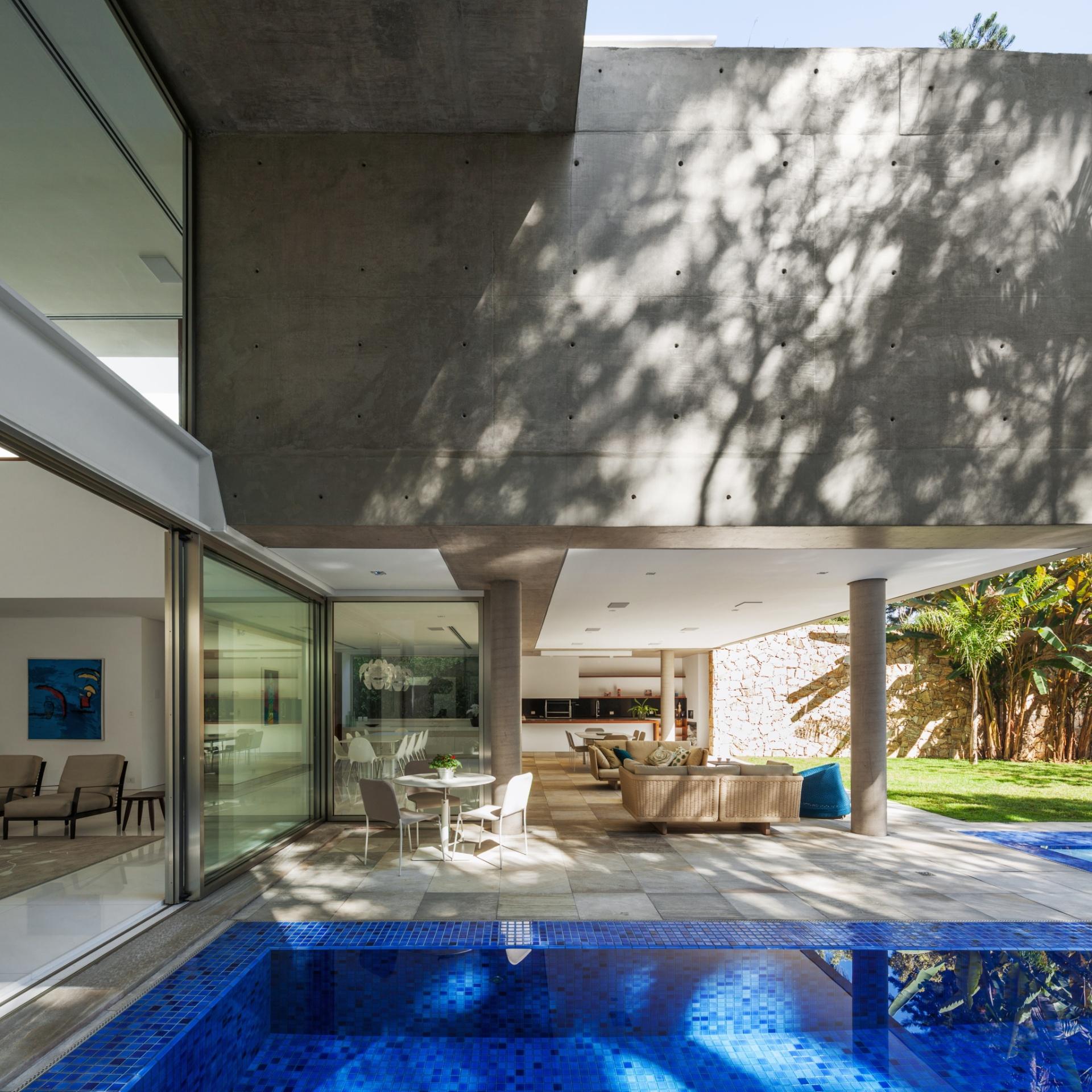 Deste ângulo, nota-se a integração da piscina com o estar e a marquise que a sombreia e protege o interior em dias de chuva. Veja que o vão da varanda é garantido por colunas esbeltas de concreto, no projeto assinado pelo escritório Reinach Mendonça Arquitetos Associados