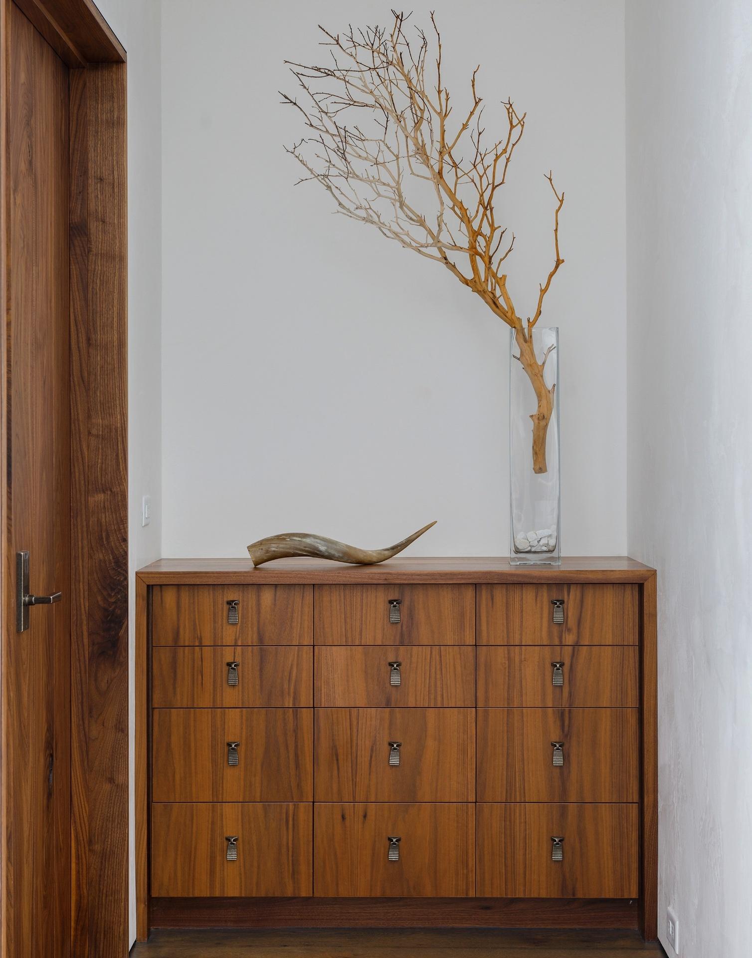 Uma cômoda organiza alguns pertences dos moradores na suíte máster. O móvel é decorado com um galho e um chifre e segue o estilo geral visto na residência (Imagem do NYT, usar apenas no respectivo material)